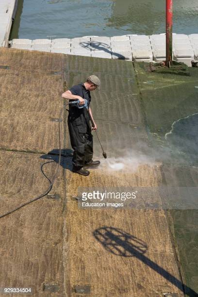 Man using a water jet to clean green algae from a concrete marina slipway Dorset England UK