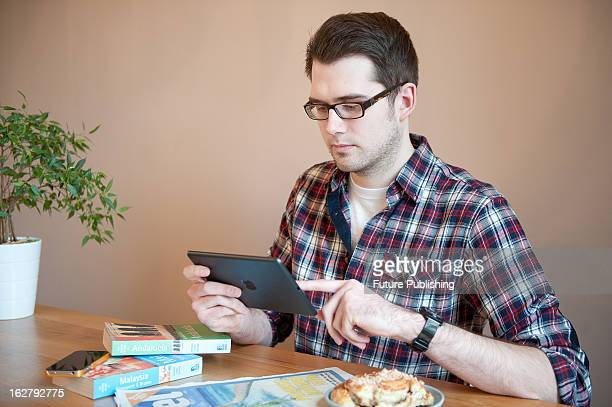 A man using an Apple iPad Mini tablet computer to research holiday destinations January 17 2013