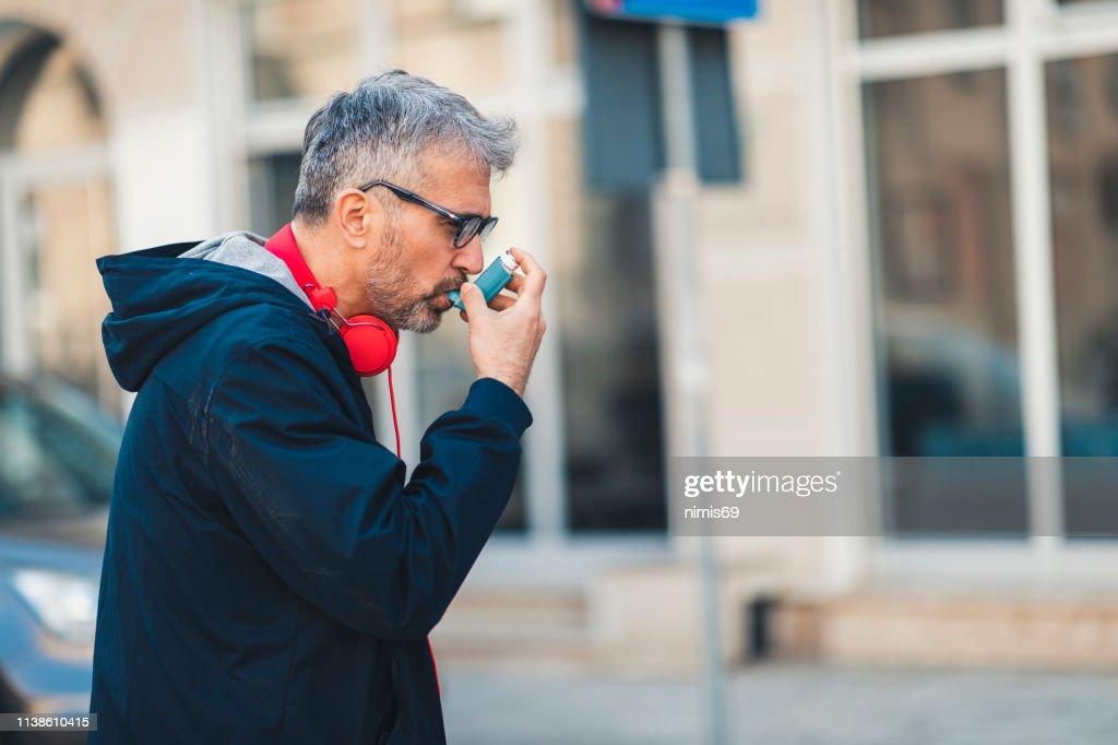 Man using an asthma inhaler : Stock Photo