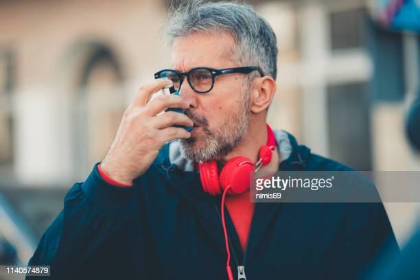 man using an asthma inhaler - copd stock photos and pictures
