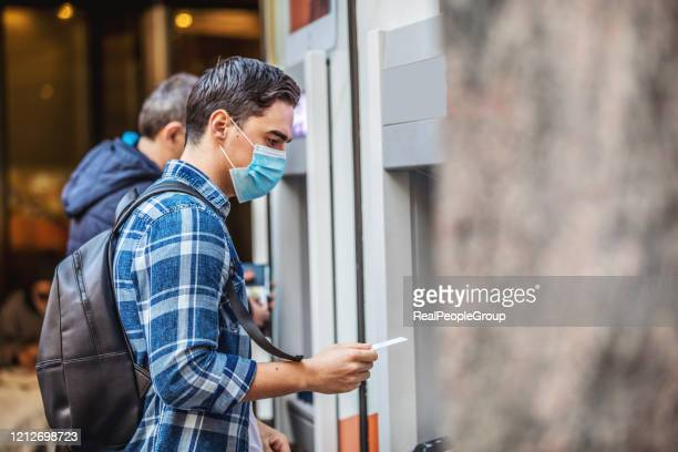 man using an cash dispenser on the street - bank stock pictures, royalty-free photos & images