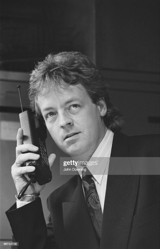 A man using an early mobile phone at the Daily Express offices in London, 20th October 1988.