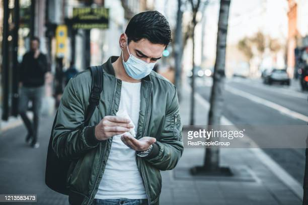 man using antibacterial hand sanitizer outdoors, closeup - antiseptic stock pictures, royalty-free photos & images