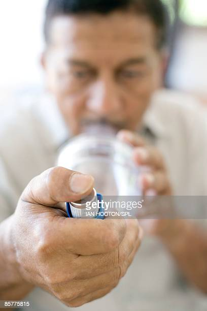 Man using asthma spacer with asthma inhaler