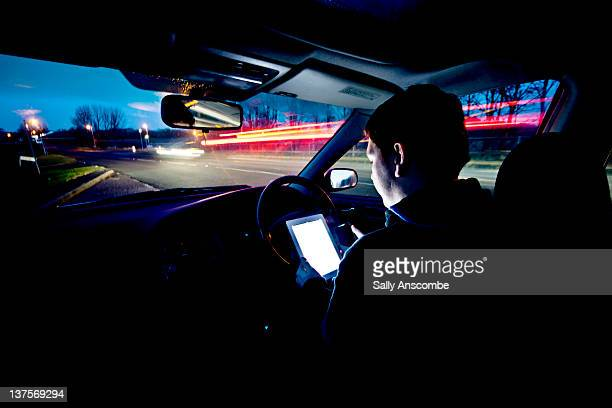 Man using at tablet and mobile phone in car