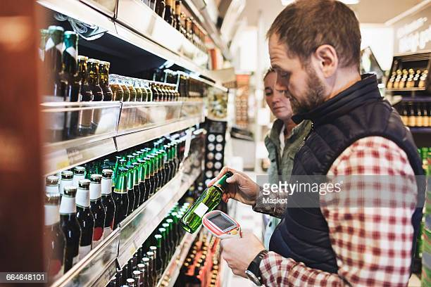 Man using bar code reader on beer bottle while standing with woman in supermarket