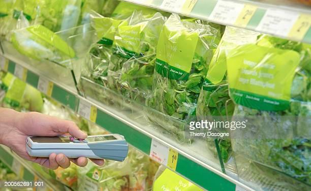 Man using barcode reader in supermarket, close-up