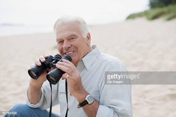 Man using binoculars at beach
