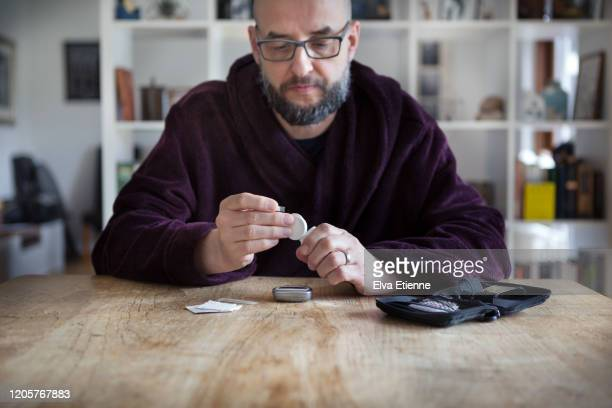 man using blood sugar measurement device to monitor diabetes - diabetes stock pictures, royalty-free photos & images