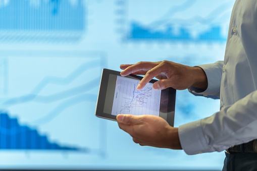 Man using business digital tablet during presentation with graphs and charts, close up - gettyimageskorea