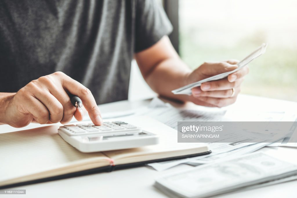 Man using calculator Accounting Calculating Cost Economic bills with money stack step growing growth saving money in home , finance concept : Stock Photo