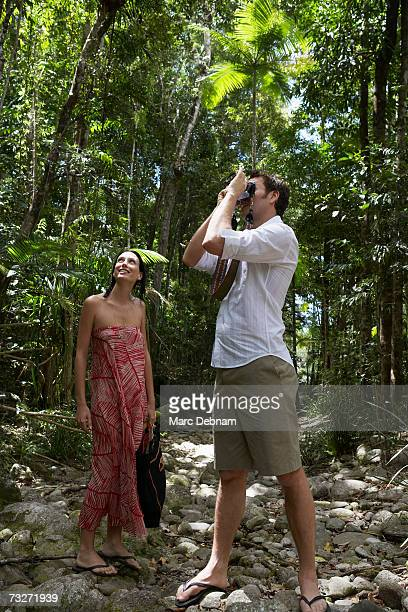 Man using camera with wife in forest