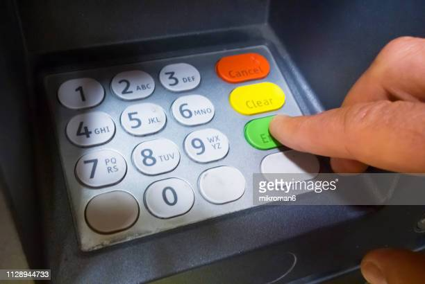 man using cash machine - money transfer stock pictures, royalty-free photos & images