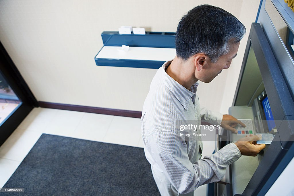 Man using cash machine : Stock Photo