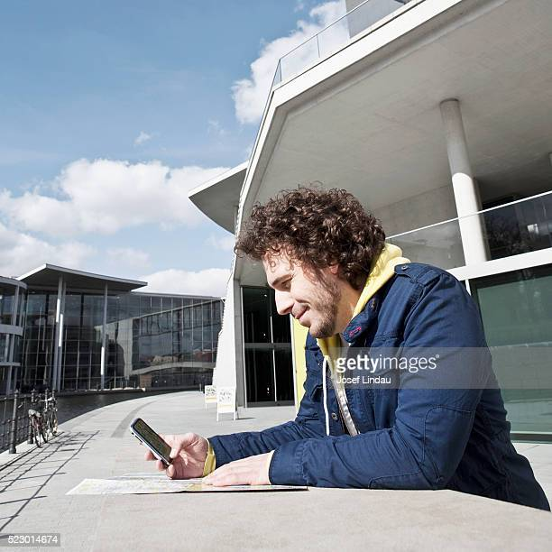 Man using cell phone and city map