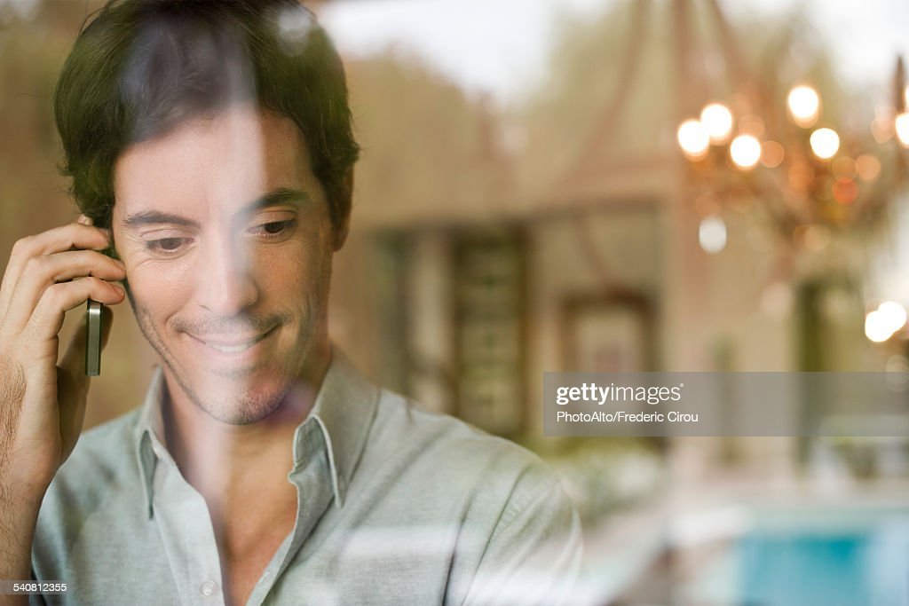 Man using cell phone at home : Stock Photo
