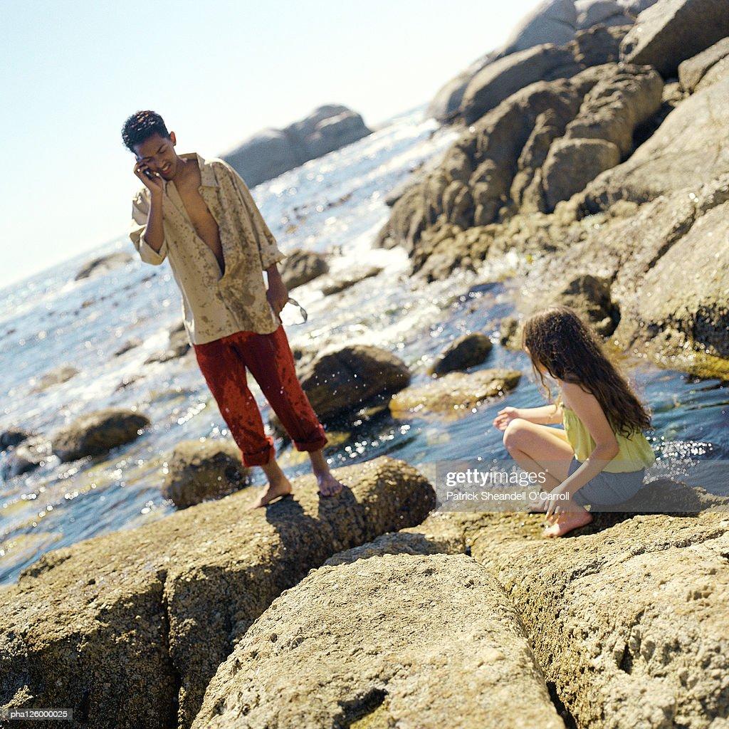 Man using cell phone, child sitting on rock : Stockfoto
