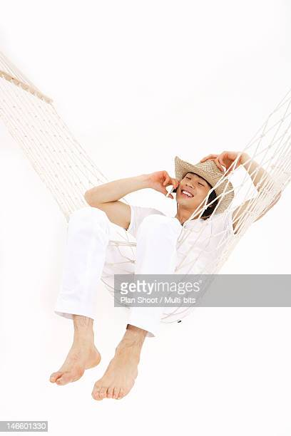 Man using cell phone in a hammock