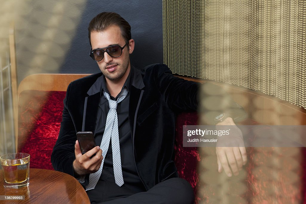 Man using cell phone in bar : Stock Photo