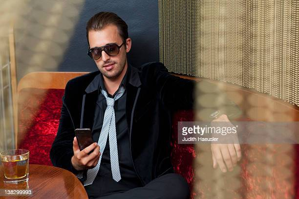 man using cell phone in bar - arrogance stock pictures, royalty-free photos & images