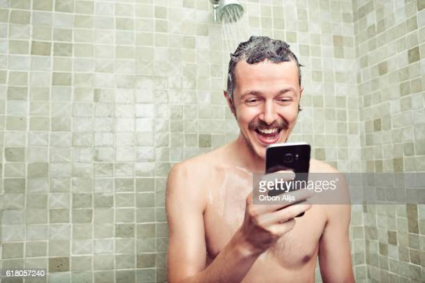 Man using cell phone in the shower