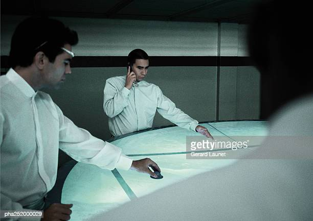 Man using cell phone, man moving object on round table