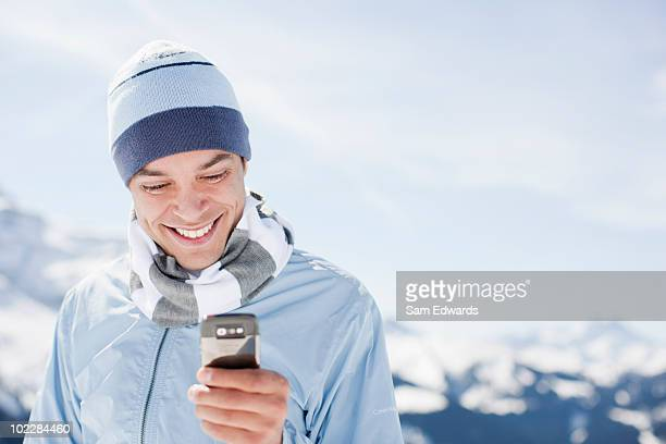 Hombre mediante teléfono móvil en la cima de la montaña