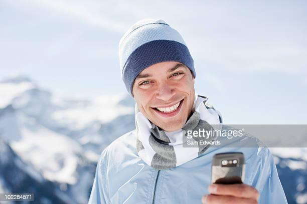 Mann mit Handy auf dem Berggipfel