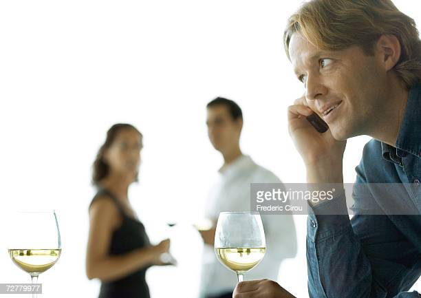 Man using cell phone, people drinking wine in background