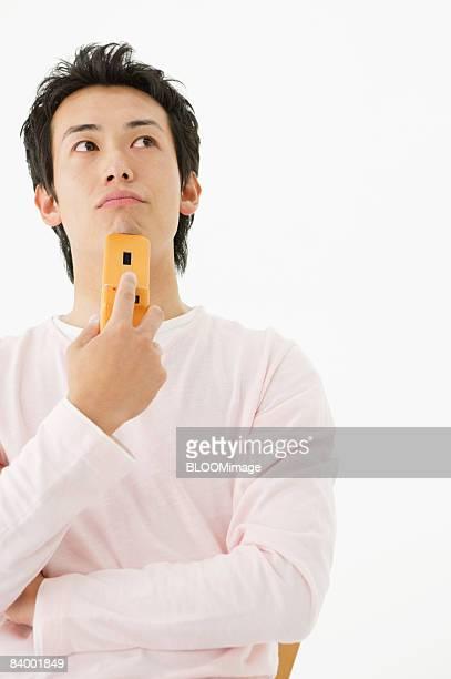Man using cellular phone, thinking, studio shot