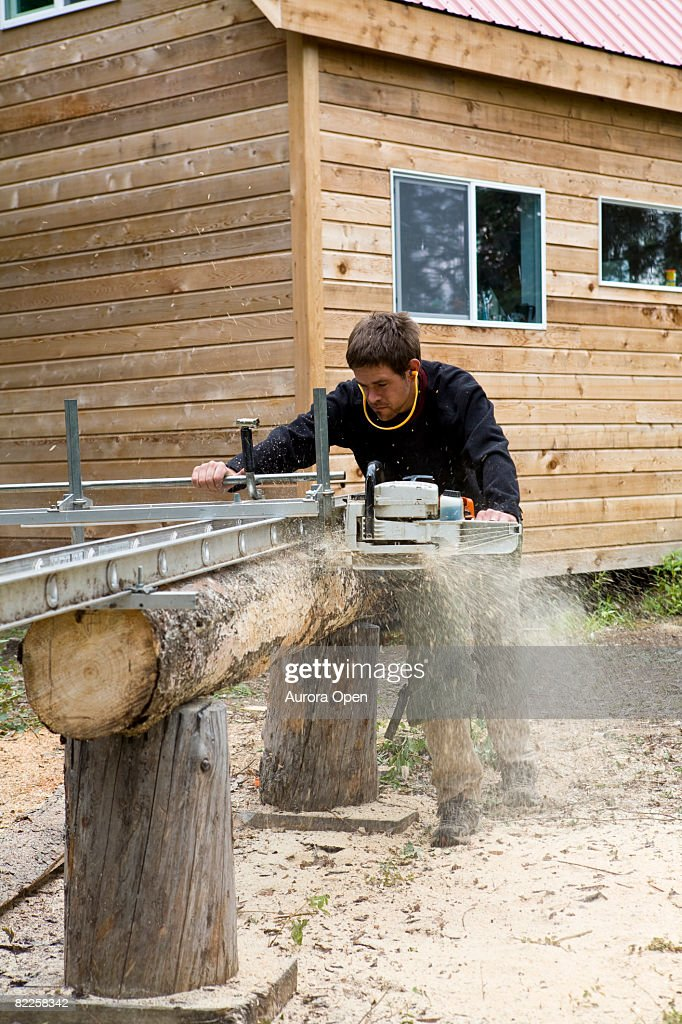 Man using chainsaw lumber maker, McCarthy, Alaska. : Stock Photo