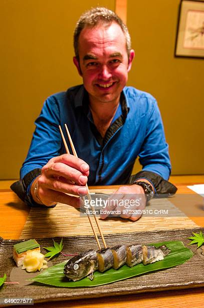Man using chopsticks to eat a river fish called Ayu stuffed with rice is called Ayu Mesi served at Kaiseki, a traditional multi-course Japanese...