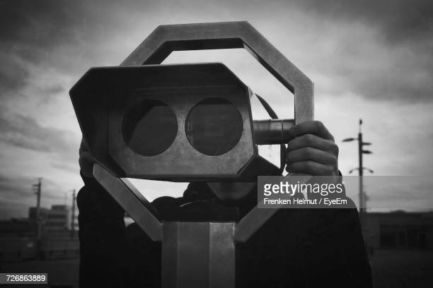 Man Using Coin-Operated Binocular Against Cloudy Sky