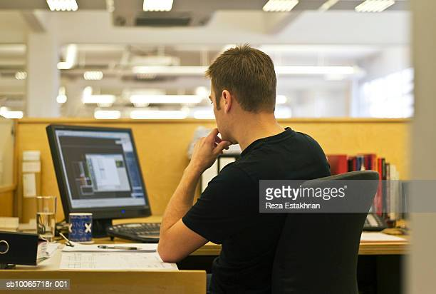man using computer in office, rear view - microsoft stock pictures, royalty-free photos & images