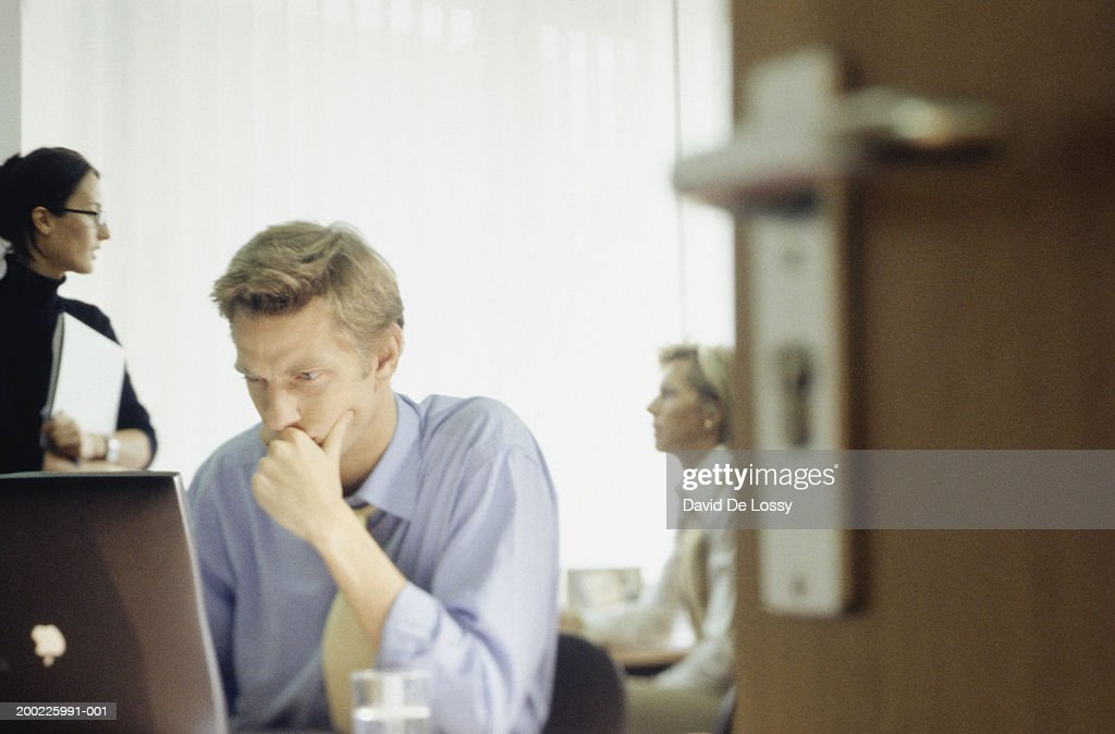 Man using computer in office, two women talking in background : Stock Photo
