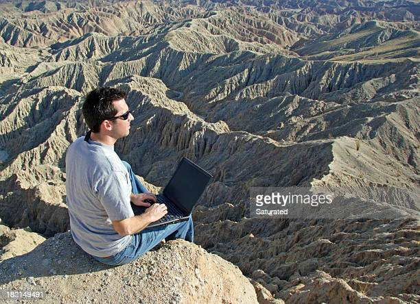 Man Using Computer in the Wilderness
