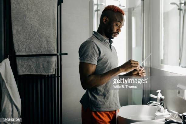 man using corona virus test swab in his bathroom - medical examination stock pictures, royalty-free photos & images