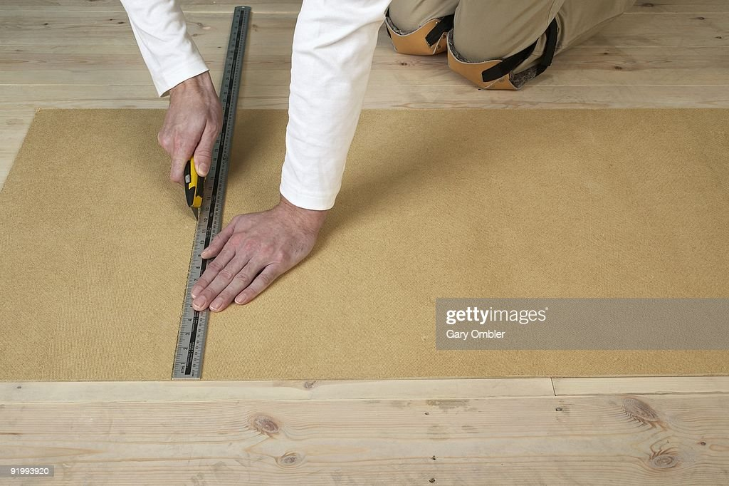 Man using craft knife and metal ruler to score line in hardboard on floorboards : Stock Photo