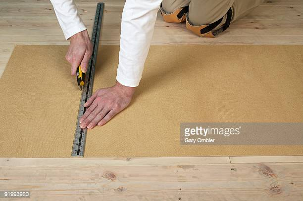 Man using craft knife and metal ruler to score line in hardboard on floorboards