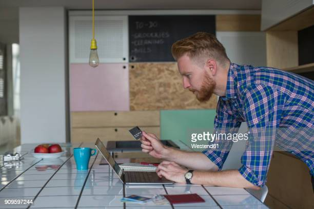 Man using credit card and laptop at home