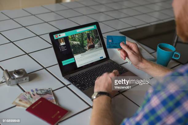 man using credit card and laptop at home - making a reservation stock photos and pictures