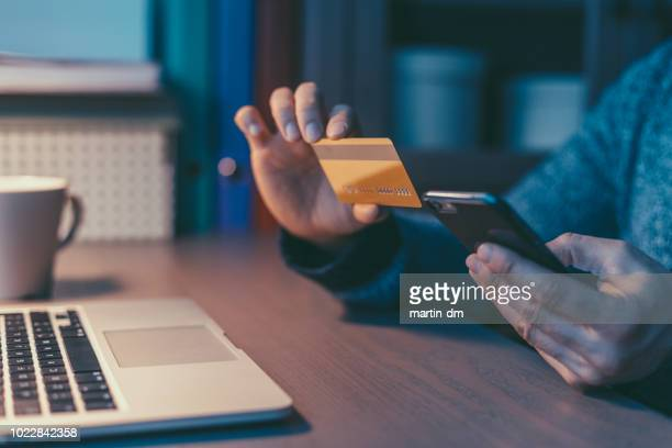 Man using credit card and smartphone for online reservation