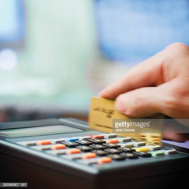 Man using credit card swipe, close-up (soft focus)