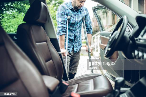 homem usando muletas está prestes a tomar o carro - dano físico - fotografias e filmes do acervo