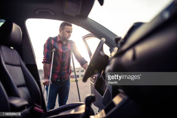 man using crutches is about to take the car - physical injury stock pictures, royalty-free photos & images