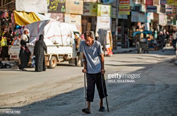 Man using crutches walks in the northern Syrian city of Raqa, the former Syrian capital of the Islamic State group, on August 21, 2019. - The...