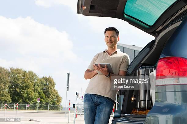 Homme à l'aide d'une tablette dans le parc de stationnement de l'aéroport