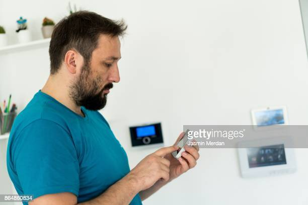 Man using digital device high tech touch screen for smart home functions