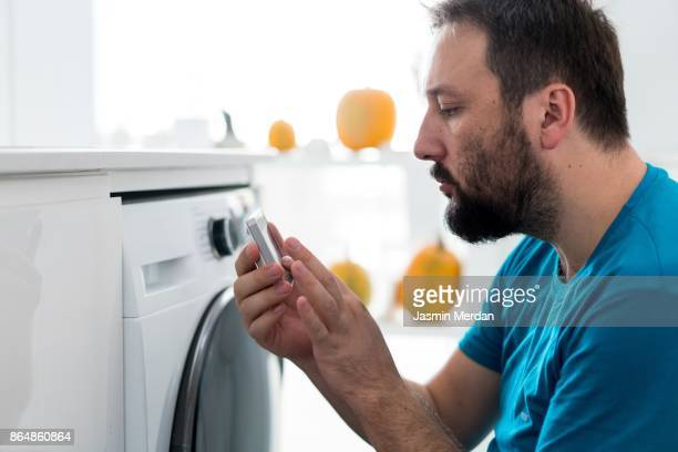 Man using digital device washing machine touch screen for smart home functions