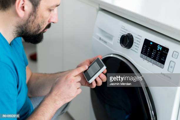 man using digital device washing machine touch screen for smart home functions - haushaltsmaschine stock-fotos und bilder